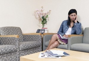 Young woman sitting in a waiting room holding a magazine
